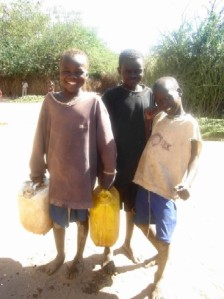 Child workers share a happy moment at the water tap.