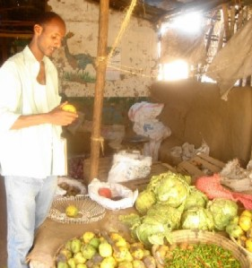 A refugee surveys vegetables in the camp market.