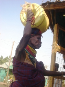 A Turkana woman carries water for sale