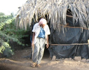 A community elder outside his home